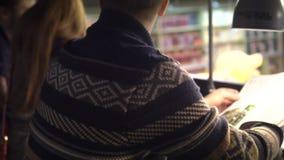 Mężczyzna w bookstore siedzi przy stołem i liśćmi przez magazynu w świetle lampy zdjęcie wideo