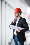 Mężczyzna w ciężkich kapeluszach przy budynkiem z planów myśleć fotografia royalty free