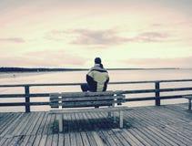 Mężczyzna w ciepłej kurtce i baseball nakrętka siedzimy na drewnianym molu i cieszymy się spokojnego ranku morze Zdjęcia Royalty Free