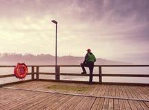 Mężczyzna w ciepłej kurtce i baseball nakrętka siedzimy na drewnianym molu i cieszymy się spokojnego ranku morze Fotografia Royalty Free