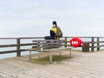 Mężczyzna w ciepłej kurtce i baseball nakrętka siedzimy na drewnianym molu i cieszymy się spokojnego ranku morze Zdjęcia Stock