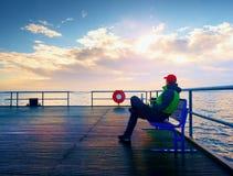 Mężczyzna w ciepłej kurtce i baseball nakrętka siedzimy na gramocząsteczki ławce i cieszymy się ranek przy morzem Fotografia Stock
