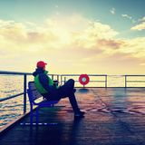 Mężczyzna w ciepłej kurtce i baseball nakrętka siedzimy na gramocząsteczki ławce i cieszymy się ranek przy morzem Obrazy Stock