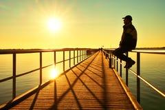Mężczyzna w ciepłej kurtce i baseball nakrętka siedzimy na molo poręcza budowie i cieszymy się ranek przy morzem Zdjęcie Stock
