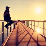 Mężczyzna w ciepłej kurtce i baseball nakrętka siedzimy na molo poręcza budowie i cieszymy się ranek przy morzem Fotografia Stock