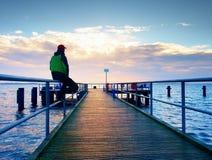 Mężczyzna w ciepłej kurtce i baseball nakrętka siedzimy na molu i cieszymy się spokojnego ranku morze Turysta relaksuje Fotografia Royalty Free