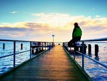 Mężczyzna w ciepłej kurtce i baseball nakrętka siedzimy na molu i cieszymy się spokojnego ranku morze Turysta relaksuje Obrazy Royalty Free