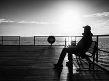 Mężczyzna w ciepłej kurtce i baseball nakrętka siedzimy na molu i cieszymy się spokojnego ranku morze Turysta relaksuje Zdjęcia Royalty Free