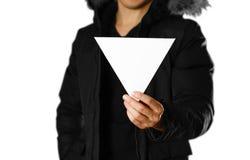Mężczyzna w ciepłej zimy kurtce trzyma trójgraniastą białą ulotkę pusty papieru z bliska pojedynczy białe tło obraz royalty free
