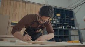Mężczyzna w ciesielka warsztacie zrobił notatkom z ołówkiem na drewnianym barze zbiory