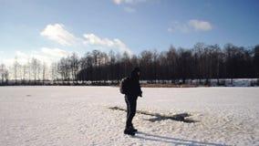 Mężczyzna w czarnej kurtce przychodził zamarznięty jezioro pływać w objawienie pańskie mrozie po to, aby, Rosyjska tradycja pływa zbiory