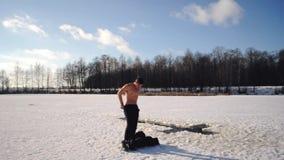 Mężczyzna w czarnej kurtce przychodził zamarznięty jezioro pływać w objawienie pańskie mrozie po to, aby, Rosyjska tradycja pływa zbiory wideo
