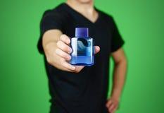 Mężczyzna w czarnej t mienia koszulowej błękitnej butelki toaletowej wodzie Zamyka up, Zdjęcie Royalty Free
