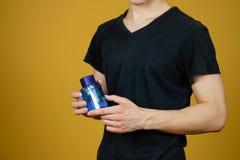 Mężczyzna w czarnej t mienia koszulowej błękitnej butelki toaletowej wodzie Zamyka up, Obrazy Stock