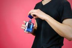 Mężczyzna w czarnej t mienia koszulowej błękitnej butelki toaletowej wodzie Zamyka up, Zdjęcia Royalty Free