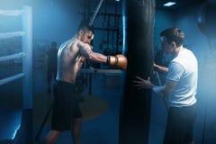 Mężczyzna w czarnych handwraps ćwiczy z torbą w gym fotografia stock