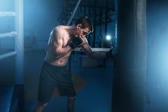 Mężczyzna w czarnych handwraps ćwiczy z torbą w gym zdjęcia royalty free
