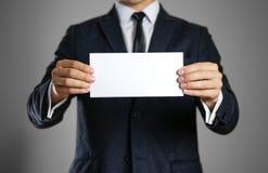 Mężczyzna w czarnym kostiumu mienia pustego miejsca jasnego bielu prześcieradło clos Zdjęcia Royalty Free
