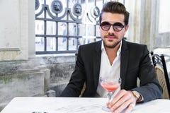 Mężczyzna w czarnym kostiumu obsiadaniu na krześle i pić koktajlu fotografia royalty free