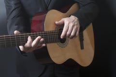 Mężczyzna w czarnym kostiumu z akustyczną klasyczną gitarą zdjęcia stock