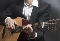 Mężczyzna w czarnym kostiumu z akustyczną klasyczną gitarą obraz royalty free