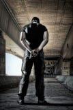 Mężczyzna w czerni maski i munduru pozyci z pistoletem Zdjęcie Stock