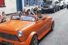 Mężczyzna w czerwonych okularach przeciwsłonecznych jedzie w małym rocznik czerwieni samochodzie Tłumów spojrzenia przy on Brickl Fotografia Royalty Free