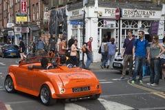 Mężczyzna w czerwonych okularach przeciwsłonecznych jedzie w małym rocznik czerwieni samochodzie Tłumów spojrzenia przy on Brickl Obrazy Royalty Free