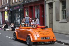 Mężczyzna w czerwonych okularach przeciwsłonecznych jedzie w małym rocznik czerwieni samochodzie Tłumów spojrzenia przy on Brickl Obraz Stock