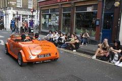Mężczyzna w czerwonych okularach przeciwsłonecznych jedzie w małym rocznik czerwieni samochodzie Tłumów spojrzenia przy on Brickl Zdjęcia Royalty Free
