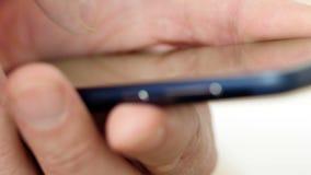 Mężczyzna w czerwonych writing sms na dotyka ekranu smartphone UltraHD wideo zbiory wideo