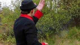 Mężczyzna w czerwonym kostiumu i czerni zapala białego papier w ręce i rzuca je w mo zbiory