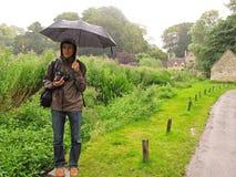 Mężczyzna w deszczu z parasolem Obrazy Royalty Free