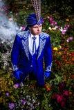 Mężczyzna w drogim zmroku - błękitny kostium iluzjonista poza na kwiat łące. Obrazy Stock