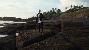 Mężczyzna w eleganckim odziewa z plecaków spacerami na skalistej czarnej piasek plaży Steadicam strza?, zwolnione tempo zbiory