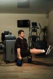 Mężczyzna w EMS kostiumu robić siedzi deskę na ciężarach Zdjęcie Royalty Free
