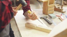 Mężczyzna w fartuch pracach z ścinakiem w ciesielka sklepie zbiory