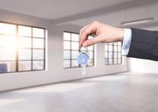 Mężczyzna w formalnym kostiumu trzyma klucz w panoramicznym mieszkaniu nowożytnego loft biurze lub Czynsz lub nowy dom biuro lub  Zdjęcie Royalty Free