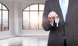 Mężczyzna w formalnym kostiumu trzyma klucz w panoramicznym mieszkaniu nowożytnego loft biurze lub Czynsz lub nowy dom biuro lub  Zdjęcie Stock