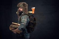 Mężczyzna w futerkowym kapeluszu trzyma cioskę i łupki Zdjęcia Stock