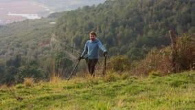 Mężczyzna w górach szuka zakopującymi i zapominającymi skarbami z jego wykrywacz metalu zdjęcia stock