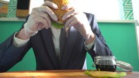Mężczyzna w garnituru i krawata łasowania hamburgerze w kawiarni zdjęcie wideo