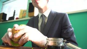 Mężczyzna w garnituru i krawata łasowania hamburgerze w kawiarni zbiory