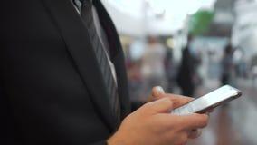 Mężczyzna w garnituru surfingu sieci na elita smartphone, uzupełnia transakcje biznesowe zbiory