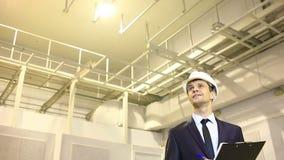 Mężczyzna w garniturze i hełmie sprawdza przesłanki konsultuje z planem zadawalający z dobrą pracą zbiory wideo