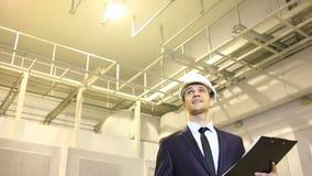 Mężczyzna w garniturze i hełmie sprawdza przesłanki konsultuje z planem zadawalający z dobrą pracą zbiory