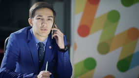 Mężczyzna w garniturze opowiada na telefonie niechętnie zbiory