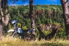 Mężczyzna w hamaku na sosnowej lasowej górze, plenerowy podróżnik relaksuje z drogowego motocyklu, enduro zdjęcia royalty free