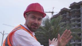 Mężczyzna w hełmie, architekt, inżynier, kierownik mówi o postępie budowa w wieczór zapasu materiału filmowego wideo zbiory