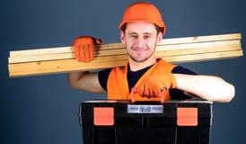 Mężczyzna w hełmie, ciężki kapelusz trzyma toolbox i drewnianych promienie, popielaty tło Cieśla, robotnik, budowniczy, woodworke Zdjęcie Stock